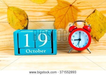 October The 19th. Blue Cube Calendar With Month And Date And Alarm Clock On Wooden Background.