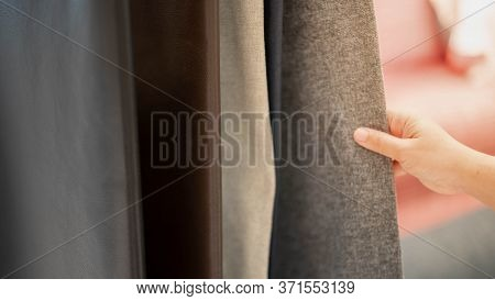 Female Hand Choosing Sheet Of Fabric Or Textile. Group Of Multi-coloured Earth Tone Fabric Swatch Fo