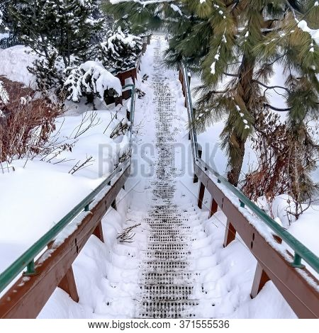 Square Frame Grate Metal Tread Stairway On Hill Slope Blanketed With Snow During Winter
