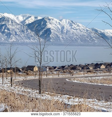 Square Frame Road And Homes Ovelooking Snowy Wasatch Mountains And Blue Utah Lake In Winter
