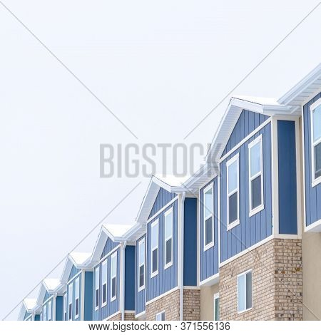 Square Crop Snowy Gable Roofs At The Facade Of Townhome With Brick Wall And Vertical Siding