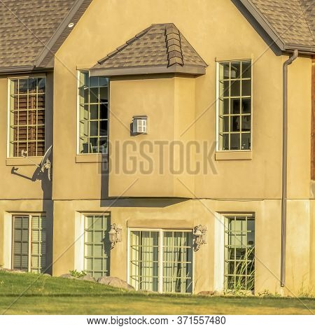 Square Frame Home With Dark Roof Shingles Concrete Brown Wall And Cottage Pane Windows