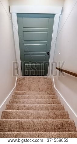 Vertical Indoor Stairs Of Home With Carpeted Treads That Leads Down To The Basement Door