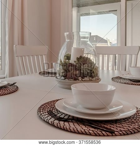 Square Frame Dining Table With Tableware And Woven Placemat Arranged Around A Centerpiece