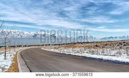 Panorama Curvy Road Amid Snowy Terrain With Scenic Wasatch Mountains And Utah Lake View