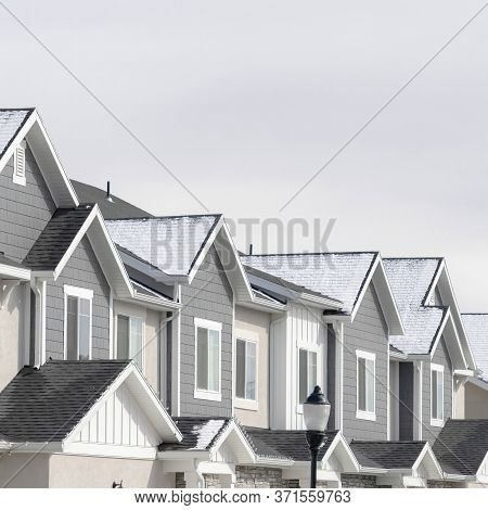 Square Facade Of Townhouses In South Jordan Utah With Snowy Gable Roofs In Winter