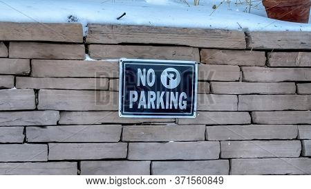 Panorama No Parking Sign On A Stone Brick Retaining Wall Topped With Snow In Winter