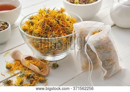 Bowl Of Dry Marigold Flowers, Tea Bags With Dry Calendula Plants. Tea Cup And Tea Kettle On Wooden T