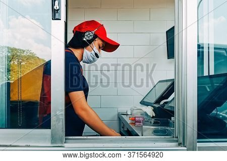 Fast Food Cashier In Drive Thru Service Wearing Hygiene Face Mask To Protect Coronavirus Pandemic Or