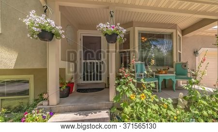 Panorama Home Exterior With Bay Window On Front Porch Decorated With Flowers And Plants