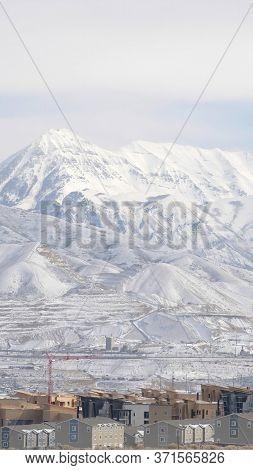 Vertical Crop Snowy Wasatch Mountain Towering Over The Neighborhood Of South Jordan In Utah