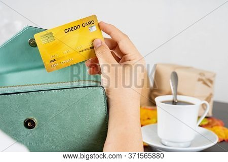 Women Hand Using A Yellow Credit Card, She Pulled The Card Out Of Her Wallet. Credit Debit Card With