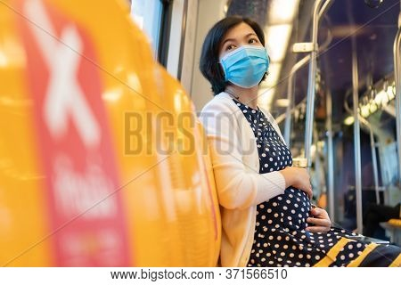 Asian Pregnant Woman Wear Face Mask Touch Her Belly And Sit On Yellow Seat In Sky Train While Go To