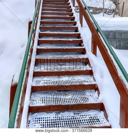 Square Outdoor Stairs With Grate Metal Treads And Green Handrail On Snowy Winter Hill