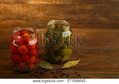 Jars Of Pickled Homemade Pickles And Cherry Tomatoes And Sprinkled On A Wooden Table.