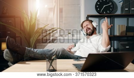 Overjoyed Businessman With Legs On Desk Listening To Music In Headphones Pretending To Play Guitar A