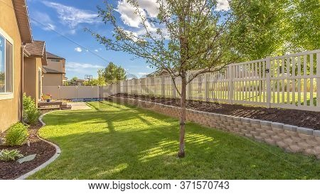 Panorama Frame Home Backyard With Vibrant Lawn And Raised Planting Bed Along White Picket Fence