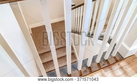 Panorama Crop White Wooden Baluster And Brown Handrail Of U Shaped Staircase Inside A Home