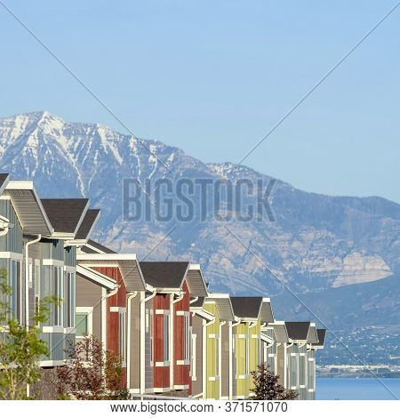 Square Townhouses Exterior With Scenic Lake And Snowy Steep Mountain Background