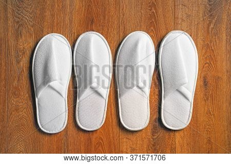 Top View Four Pairs Of New Soft White Slipper In The Hotel On Wooden Floor. Four White Slipper, Isol