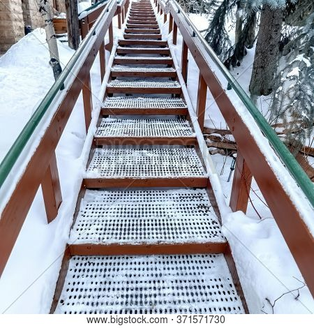 Square Crop Focus On Stairs With Grate Treads And Metal Handrails Against Snow Covered Hill
