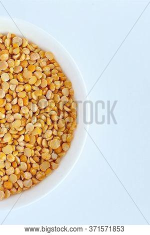 Split Yellow Peas In A Wooden Spoon On Split Yellow Peas