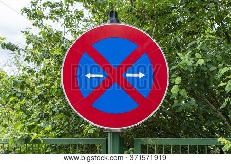 Road Sign Stop Prohibited. Arrows To Indicate The Direction Of The Traffic Sign. Above The Iron Fenc