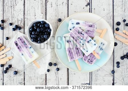 Blueberry Vanilla Yogurt Ice Pops. Top Down Table Scene With A White Wood Background.