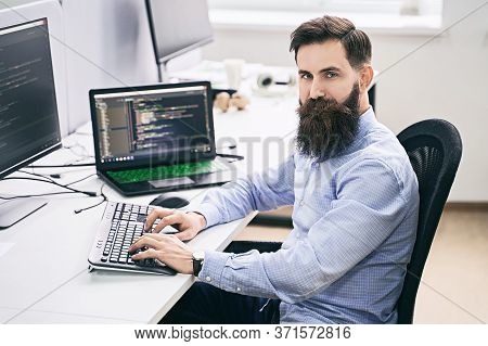 Serious Computer Programmer Developer Working In It Office, Sitting At Desk And Coding, Working On A