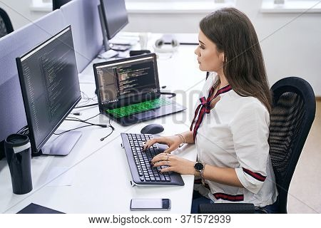 Beautiful Female Junior Software Developer Working On Computer In It Office, Sitting At Desk And Cod