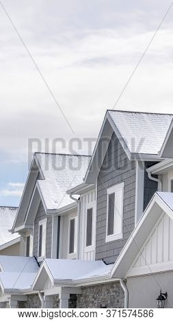 Vertical Facade Of Snowy Townhouses In South Jordan Utah Against Cloudy Sky In Winter