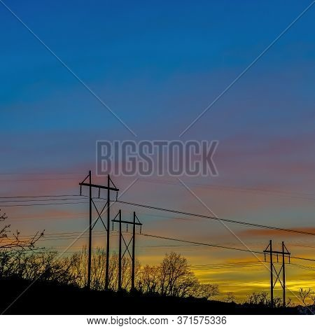 Square Crop Electricity Posts Silhouetted Against Blue Sky In Provo Canyon Utah At Sunset