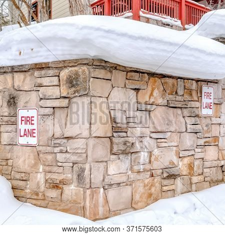 Square Frame Stone Retaining Wall With Fire Lane Sign On A Hill With Thick Snow In Winter