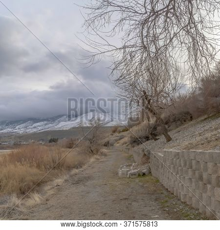 Square Frame Dirt Road Along The Retaining Wall Of Slope Overlooking Lake And Snowy Mountain