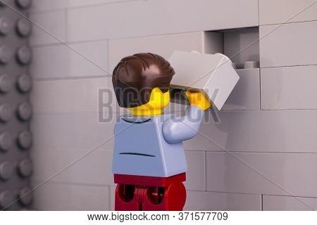Tambov, Russian Federation - June 07, 2020 Lego Man Minifigure With Brick Ready To Finishing Gray Wa