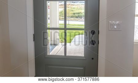 Panorama Front Door With Balck Knob And Glass Panes Against White Wall And Wood Floor