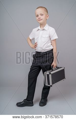 Cute Short-haired Boy Boy 7 Years Old With Black Suitcase, Looking Into The Camera. Gray Background.