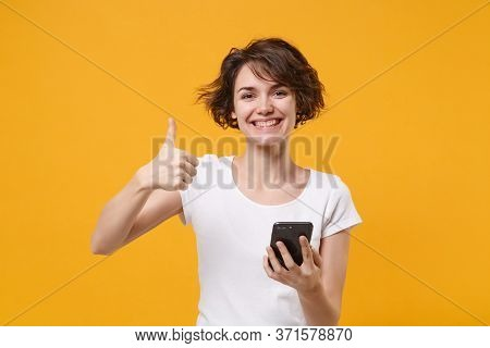 Smiling Young Brunette Woman Girl In White T-shirt Posing Isolated On Yellow Orange Wall Background