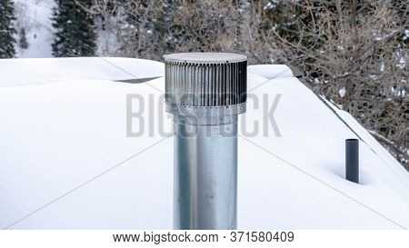 Panorama Frame Shiny Metal Chimney Vent Pipe On The Roof Of Home Covered With Snow In Winter