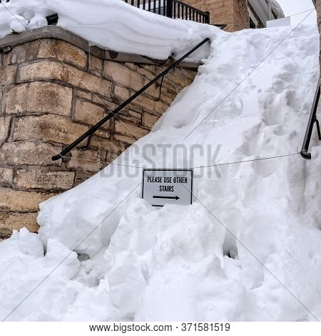 Square Snowed In Stairs Amid Stone Retaining Wall With Home And Cloudy Sky Background