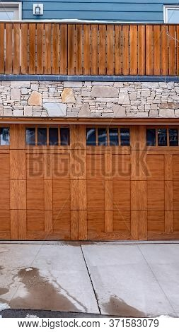 Vertical Crop Brown Wooden Glass Paned Garage Door Against Stone Wall Under Balcony Of Home