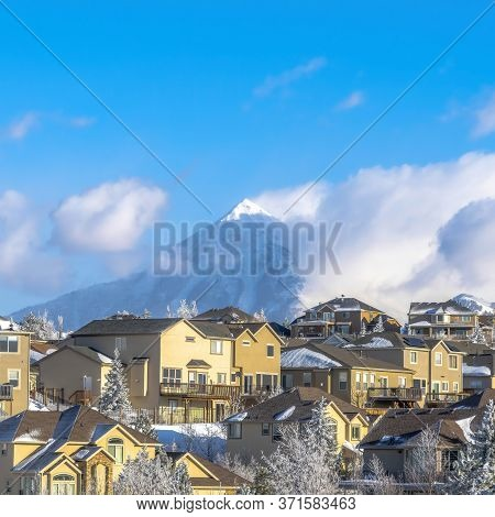 Square Frame Homes On Frosted Neighborhood Setting With View Of Snowy Wasatch Mountains