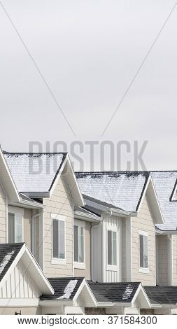 Vertical Crop Townhouses With Snowy Gable Roofs In South Jordan Utah On A Cloudy Winter Day