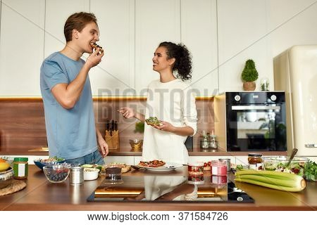 Happy Couple, Vegetarians Cooking Breakfast In The Kitchen. Young Man And Woman Tasting Sandwiches T