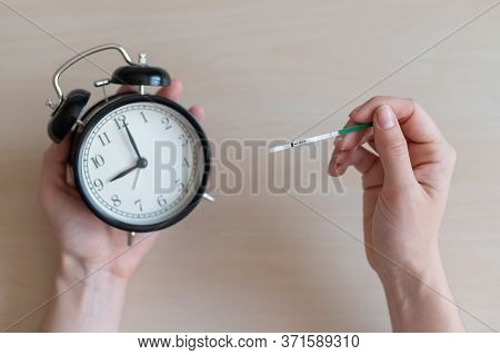 Woman Holds A Negative Pregnancy Test And Alarm Clock. Female Fertility Biological Clock Concept. On