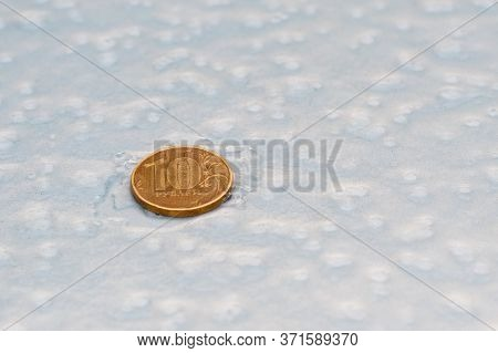 A Coin Of Ten Rubles Is On The Ice Surface. Freezing Ruble