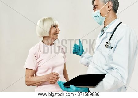 Good News. Mature Male Doctor In Medical Uniform And Protective Mask Talking With Happy Senior Femal