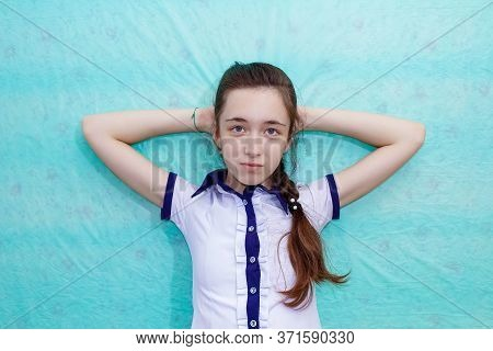 A School Girl With A Long Braid Sits Leaning Against The Wall And Putting Her Hands Behind Her Head.