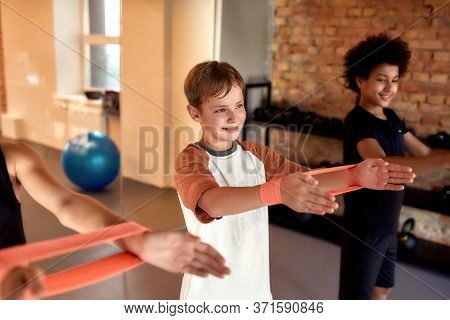Caucasian Boy Working Out Using Resistance Band Together With Other Kids In Gym. Focus On A Caucasia