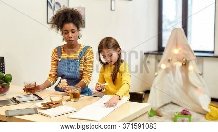 African American Woman Baby Sitter Entertaining Caucasian Cute Little Girl. Kid Is Drawing While Hav